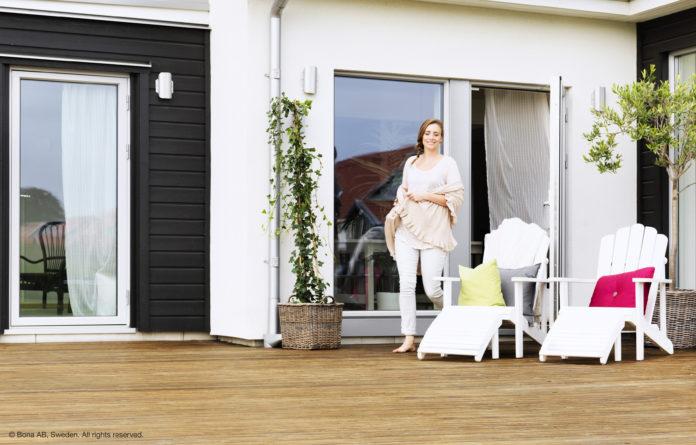 mujer saliendo a su terraza de suelo madera